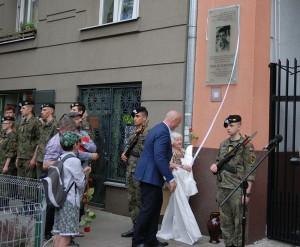 Tablicę odsłania inicjatorka tablicy w towarzysstwie Burmistrza Tomasza Kucharskiego
